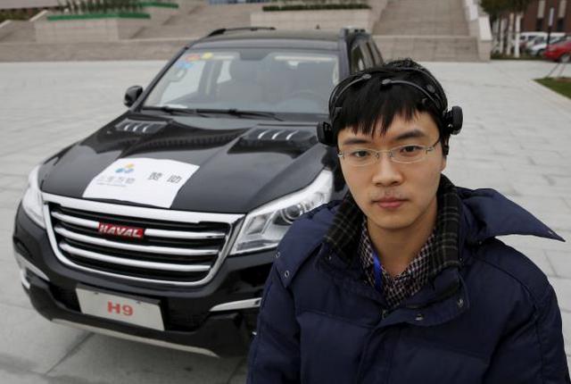 Peneliti Zhang Zhao mengenakan peralatan sinyal membaca otak berpose dengan mobil Haval H9 yang dapat dikontrol dengan gelombang otaknya
