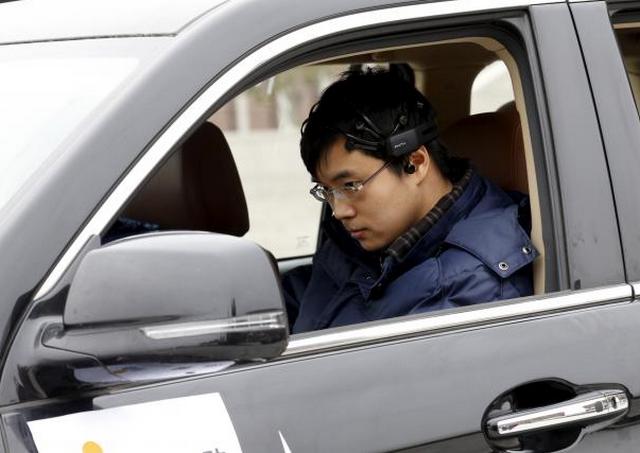 Peneliti Zhang Zhao mengenakan peralatan sinyal-membaca otak mempersiapkan untuk memindahkan mobil dengan gelombang otaknya